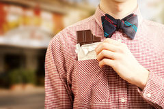 Man taking chocolate out of pocket at street Royalty Free Stock Images