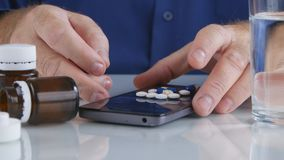 Man Taking Colorful Pills from Cellphone Screen Surface stock photos