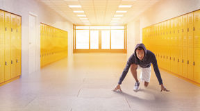 Man taking crouch start. Man in hoodie taking crouch start in school lobby. Fitness Gym. Concept of physical education and fitness. 3d rendering. Toned image Stock Photos