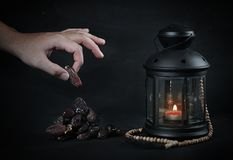Man Taking Dates. Ramadan Candle Lantern with Wooden Prayer Bead. S Royalty Free Stock Images