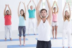 Man taking a deep breath. Young men taking a deep breath during yoga session in white studio stock photo