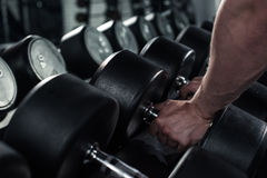 Man taking dumbbells for exercising at gym Stock Image