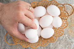 Man taking an egg from an Easter basket Royalty Free Stock Image
