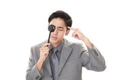 Man taking an eye test. Asian man with an eye paddle royalty free stock image