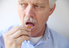 Man taking fish oil pill Stock Photography