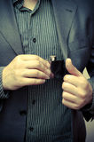 Man taking a flask out of his suit pocket Stock Photo