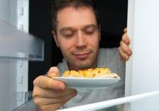 Man taking food. Man taking food out of refrigerator at night Royalty Free Stock Image