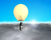 Man taking glowing lamp balloon flying over clouds Royalty Free Stock Photography
