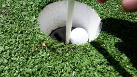 Man taking golf ball out of cup after a successful hole in one stock footage