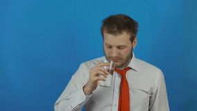Man taking a headache pill due to hangover after alcohol party or hard day`s work stock video footage