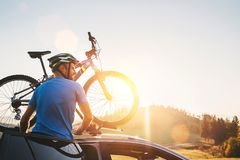 Man taking his bicycle from car roof. Mountain biking concept royalty free stock image