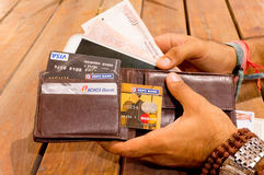 Man taking indian payment options out of a wallet. Delhi, India; 26th Apr 2015: Man taking out indian payment options like cash, credit cards and mobile phone Stock Photos