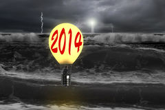Man taking lamp balloon with dramatic ocean, lightning and light. Man taking glowing lamp balloon with dramatic ocean, lightning and lighthouse Royalty Free Stock Images
