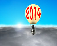Man taking lamp balloon floating over clouds, looking at sun Royalty Free Stock Images