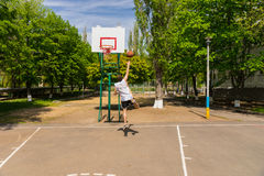 Man Taking Lay Up Shot on Basketball Court. Young Athletic Man Taking Lay Up Shot on Basket on Basketball Court in Lush Green Park royalty free stock photography