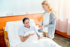Man taking medicines and woman holding glass of water Royalty Free Stock Image