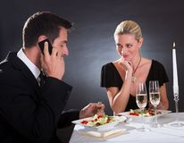 Man taking a mobile call during dinner Royalty Free Stock Images