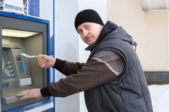 Man is taking money at ATM Stock Photos