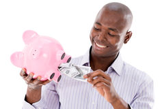 Man taking money from a piggybank Royalty Free Stock Photos