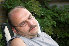 Man taking a nap. Mature man taking a nap in the garden Royalty Free Stock Image