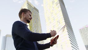 Man taking notes in folder on the city street at urban modern lanscape and lookinf at sides. Young man with ring binder taking notes in his documents outdoor and stock video footage
