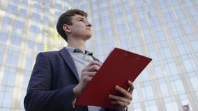 Man taking notes in folder on the city street at urban modern lanscape. Young man with ring binder taking notes in his documents outdoor stock footage