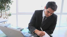 Man taking notes while looking his computer stock footage