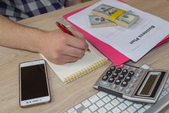 Man, taking notes. Man with dollars, Cash on the table. Profits, savings. Stack of dollars. Success, motivation, financial flows, Royalty Free Stock Images