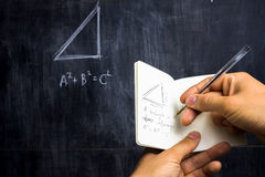Man taking notes of math theorem on blackboard. In his notebook Royalty Free Stock Images