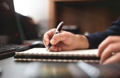 Man Taking Notes on Notebook and Doing Plans on Work Desk. In Office stock photography