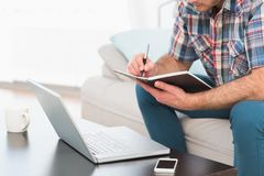 A man taking notes notebook sitting on a sofa Royalty Free Stock Photography