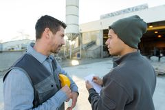 Man taking notes from worker on factory site. Factory Stock Images