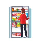Man taking out juice from the open refrigerator Stock Photography