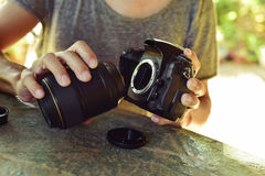 Man taking out the lens of his camera. Closeup of a young caucasian man taking out the lens of his reflex camera outdoors Stock Image