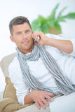 Man taking phone call whilst on sofa Stock Photography