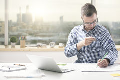 Man taking phone out of pocket. Attractive young man sitting at office desk with laptop and taking smartphone out of shirt pocket Royalty Free Stock Images