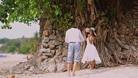 Man takes photo of beautiful woman in hat and white dress on a camera Outdoors Under the Tree with roots. Happy smiling stock footage