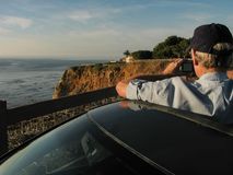 Man taking photo from car sunroof on scenic coastal roadtrip stock images