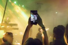 Man taking photo at concert stock photos