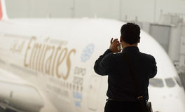 Man taking photo of docked Emirates Airbus A380 Stock Images