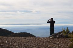Man taking a photo of a foggy landscape. In the mountain Royalty Free Stock Images