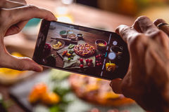 Man is taking photo frash and tasty pizza on wooden table Royalty Free Stock Photo