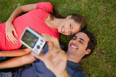 Man taking a photo with his friend while lying side by side Royalty Free Stock Photo