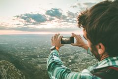 Man taking a photo with his mobile phone to a sunset. Guy taking a picture of a sunset in the mountains royalty free stock images