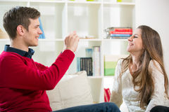 Man taking photo of his pretty girlfriend in the living room Stock Photos