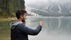 Man taking photo at lake with action cam. Young handsome man taking photo or recording video with action cam at lake in forest, by the shore. Braies lake or stock video