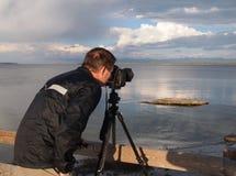 Man taking photo of lake with camera mounted on tripod Stock Photos