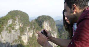 Man Taking Photo Of Mountain Landscape On Cell Smart Phone Showing To Tourists Group Talking stock video footage
