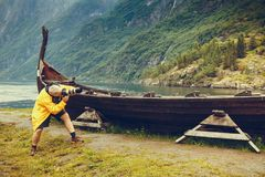 Man taking photo from old viking boat in norway. Male tourist with camera taking photo of old wooden viking boat on seashore in norwegian nature, foggy misty day Stock Photography