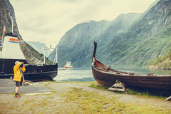 Man taking photo from old viking boat in norway Stock Photography